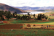 PERU, HIGHLANDS, CUZCO AREA View across traditional village and fields between Chinchero and Maras