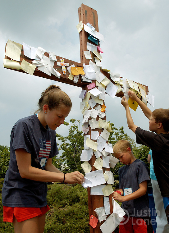 A young girl (L) and two boys tack pieces of paper describing their sins to a wooden cross before taking part in an outdoor baptizing at Willow Creek Community Church in South Barrington, IL on June 26, 2005. The church holds regular mass baptisms at which hundreds of people are baptized in the church's small lake.