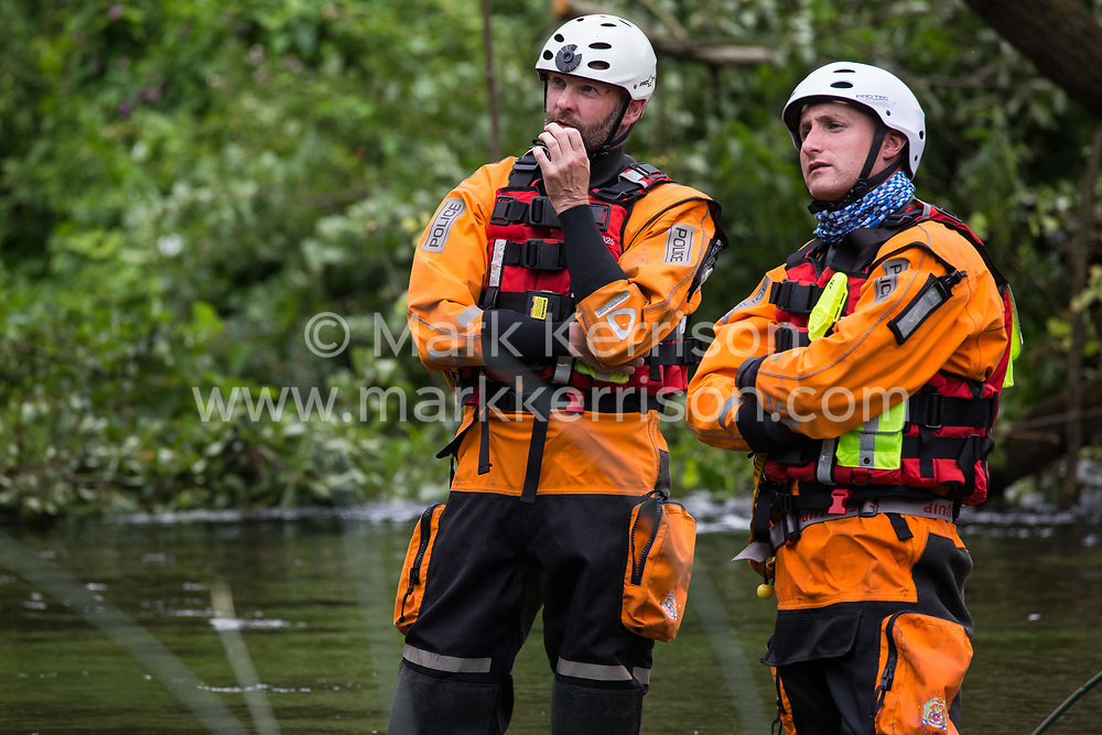 Denham, UK. 24 July, 2020. Police officers from Hampshire Police Marine Support Unit standing in the river Colne observe environmental activists from HS2 Rebellion who had been trying to hinder the destruction of an ancient alder tree in connection with works for the HS2 high-speed rail link in Denham Country Park. A large policing operation involving the Metropolitan Police, Thames Valley Police, City of London Police and Hampshire Police as well as the National Eviction Team was put in place to enable HS2 to remove the tree.