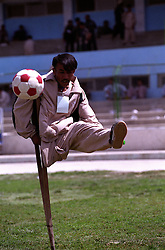 A disable athlete plays football while holding himself on a crutch...On 23-25 August 2005, Special Olympics Afghanistan held its first national Games at Olympic Stadium in Kabul. ..More than 300 athletes, including 80 female athletes, experienced a taste of happiness and achievement for the first time in their lives. They competed in athletics, bocce and football (soccer). Because of cultural restrictions, males and females competed at separate venues...