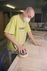 Cabinet maker sanding down blanket box using D A Sander,