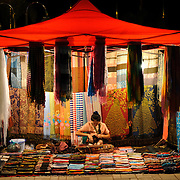 A vendor mans her stall under a tent selling textiles at the night market on Quai Fa Ngum on the banks of the Mekong in Vientiane, Laos.