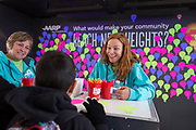 AARP's Carly Roszkowski talks with an attendee at the commitment wall at the AARP Block Party at the Albuquerque International Balloon Fiesta in Albuquerque New Mexico USA on Oct. 7th, 2018.