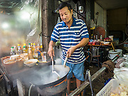 26 MAY 2015 - BANGKOK, THAILAND: A man makes an order of Pad Thai (fried noodles) at his small restaurant on Sukhumvit Soi 38 in Bangkok. He has had the restaurant for more than 30 years and has to close in the next months. The food carts and small restaurants along Soi 38 have been popular with tourists and Thais alike for more than 40 years. The family that owns the land along the soi recently decided to sell to a condominium developer and not renew the restaurant owners' leases. More than 40 restaurants and food carts will have to close. The first wave of closings could start as soon June 21 and all of the restaurants are supposed to close over the next several months.     PHOTO BY JACK KURTZ