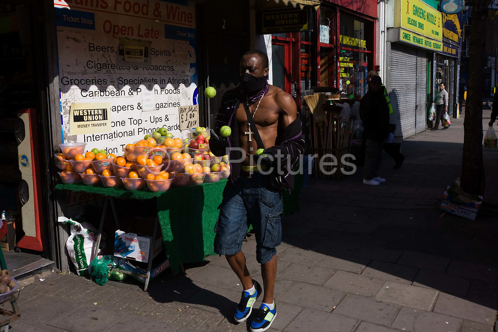 A man walks down a street practicing the form of juggling called three-ball cascade. Walking past a stall of oranges and apples, the tennis balls are seen in mid-air, having been thrown from one hand, to land in the other. The juggler starts with two balls in one hand and the third ball in the other hand. One ball is thrown from the first hand in an arc to the other hand. Before catching this ball the juggler must throw the ball in the receiving hand, in a similar arc, to the first hand. Because the hands must move up and down when throwing and catching, putting this movement together causes the left hand to move in a counter clockwise motion, and the right hand to move in a clockwise motion.