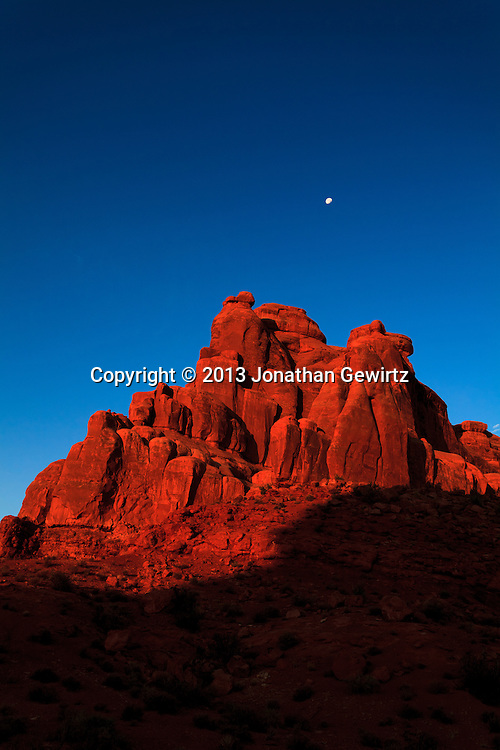 The rising sun illuminates red rocks in Arches National Park, Utah. WATERMARKS WILL NOT APPEAR ON PRINTS OR LICENSED IMAGES.<br /> <br /> Licensing: https://tandemstock.com/assets/52711279