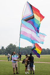 London, UK. 24th July, 2021. LGBTI+ protesters hold Progress Pride and Transgender Pride flags as the first-ever Reclaim Pride march arrives in Hyde Park for a Queer Picnic. Reclaim Pride replaced the traditional Pride in London march, which many feel has become too commercial and strayed from its roots in protest, and was billed as a People's Pride march for LGBTI+ liberation.