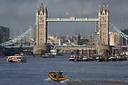 A 'Thames Rib Experience' pleasure boat heads upriver towards Tower Bridge on the river Thames, on 17th January 2020, in London, England.