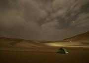 A team member sleeps in his tent in the desert.