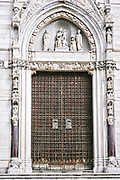Doors on the Duomo di Napoli, or Naples Cathedral in Naples, southern Italy. The present cathedral was commissioned by King Charles I of Anjou. Construction continued during the reign of his successor, Charles II (1285-1309) and was completed in the early 14th century under Robert of Anjou.