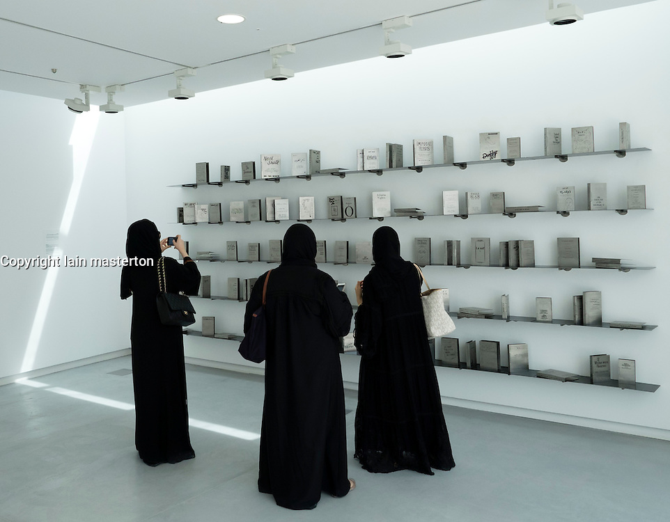 Visitors looking at exhibit by Shilpa Gupta entitled Someone Else a collection of stainless steel etched books on opening day of the 11th Sharjah Biennial Art festival in United Arab Emirates