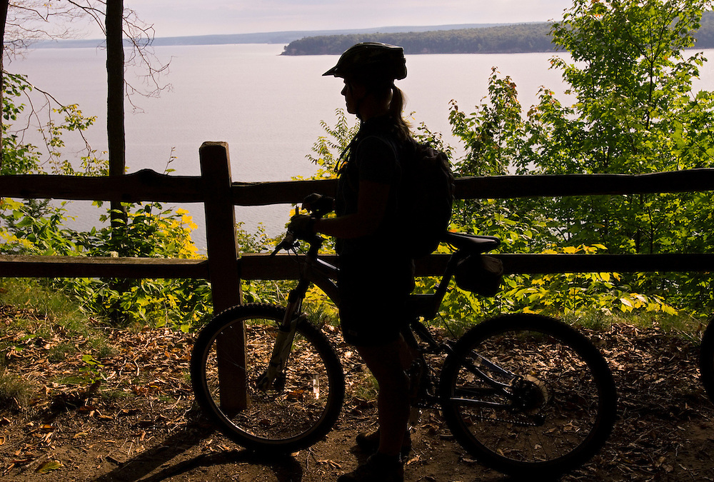 A mountain biker stops at an overlook of Trout Bay on Grand Island National Recreation Area in Munising Michigan.
