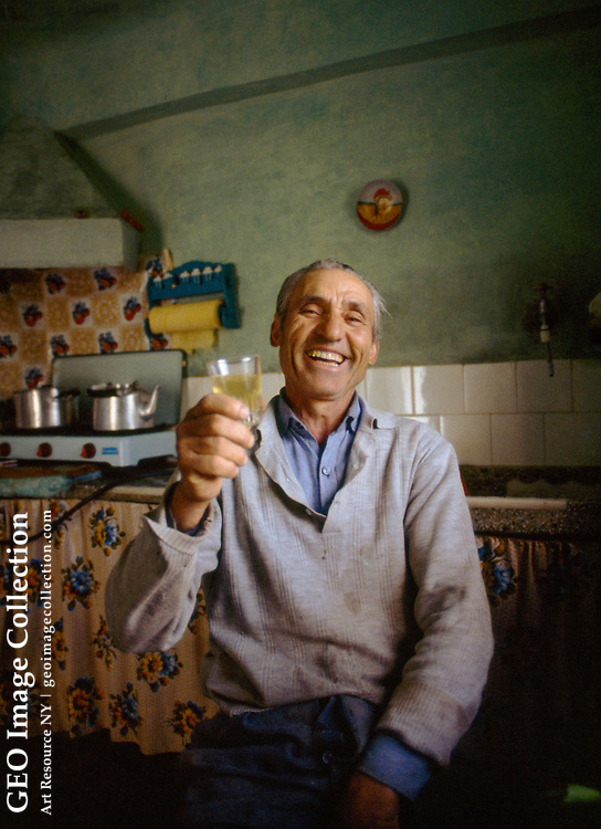 Portrait of Georgios Bafas toasting with a glass of ouzo.