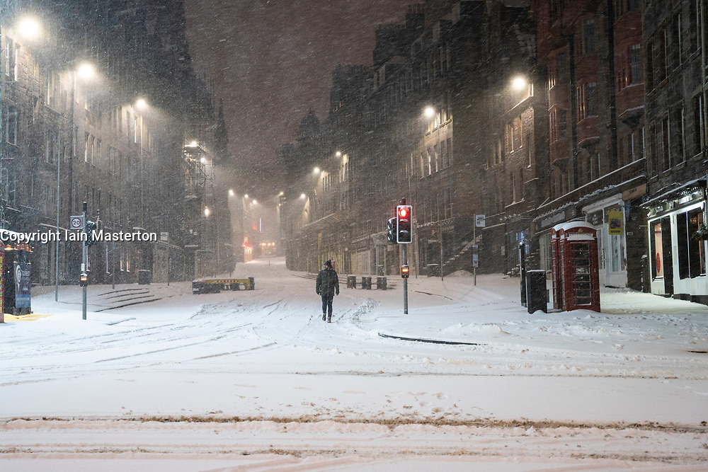 Edinburgh, Scotland, UK. 10 Feb 2021. Big freeze continues in the UK with heavy overnight and morning snow in the city. Pic; Lone member of public on the Royal Mile at Lawnmarket in the early morning snow blizzards. Iain Masterton/Alamy Live news