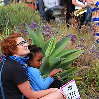 Julianne Wagar and her daughter Matilda listen to a speaker at the Juneteenth event in downtown Santa Cruz on Friday. (Shmuel Thaler — Santa Cruz Sentinel)