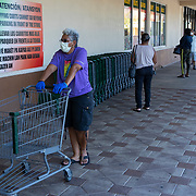 Customers practice social distancing as they wait to enter the Fancy Fruit and Produce grocery store on Friday, April 3, 2020 in Orlando, Florida. The store is allowing ten people at a time to shop for their needs. (Alex Menendez via AP)