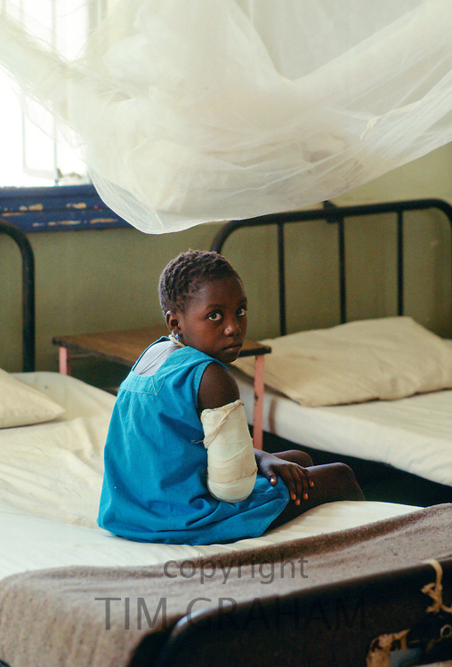 Young girl with arm in plaster bandage sits on a bed in a rural hospital supported by  the Save the Children Fund charity in The Gambia, West Africa.  A mosquito net hangs above.