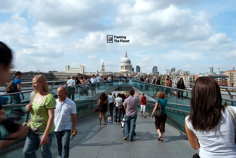 This image shows the new and ultra modern millennium bridge as it leads onto the contrasting historic St Pauls Cathedral, London. This is the newest crossing point of the river Thames and is in the heart of the city running from the South Bank near to all the famous tourist sites to St Pauls near the City of Westminster. <br /> <br /> The bridge is only for pedestrians and had its famous bounce not long after opening. This photo was taken right in the heart of the action from within the crowds of people walking and crossing the bridge on a bright summers day. This image is ready to download for commercial editorial use.
