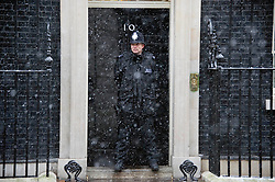 A policeman keeping out of the way of a snow shower whilst guarding No 10 Downing Street, London, UK, January 18 2013. Photo by  i-Images.