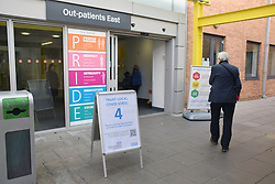 Outpatients entrance, Norfolk & Norwich Universities Hospital NHS Trust with Covid-19 warning signs, Norwich UK December 2020