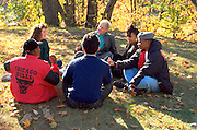 Multiethnic group of high school friends age 15 sitting in circle talking in city park.  St Paul Minnesota USA