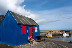 Colourful wooden hut by harbour in fishing village of St Abbs on North Sea coast in Scottish Borders, Scotland, UK