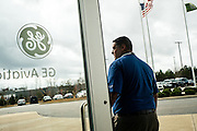 """AUBURN, AL – NOVEMBER 20, 2016: Ricardo Acevedo, plant manager at General Electric's Auburn facility, stands outside the newly built plant in Auburn's West Technology Park. Acevedo says GE chose Auburn in 2014 as their first site to use 3D printing to make high-volume products because it could count on an educated workforce and include the university as a partner in research. Currently GE is printing 50,000 jet engine nozzles a year using 30 3D printing machines, with intentions of doubling the machines in 2017. """"We need to understand the properties of the metal powder to get more consistent results,"""" Acevedo said. <br /> <br /> In much of the United States, global trade and technological innovation has failed to produce the prosperity hoped for by political and business leaders. Yet despite formidable economic challenges, some localities are flourishing. In Lee County, Ala., unemployment is below the national average despite the loss of thousands of manufacturing jobs, and the key to the county's resilience may be Auburn University, which provided a steady source of employment during recessions and helped draw new businesses to replace those that fled. CREDIT: Bob Miller for The Wall Street Journal<br /> [RESILIENT]"""