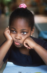 Young girl sitting at desk in classroom looking bored,