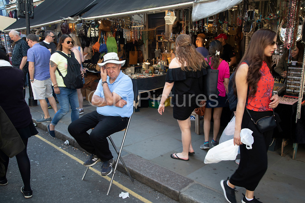 Antique stallholder sits on a stool outside his shop at Portobello Road Market in Notting Hill, West London, England, United Kingdom. People enjoying a sunny day out hanging out at the famous Sunday market, when the antique stalls line the street.  Portobello Market is the worlds largest antiques market with over 1,000 dealers selling every kind of antique and collectible. Visitors flock from all over the world to walk along one of Londons best loved streets.