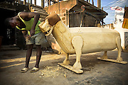 Coffin maker Adjei Dennis carves the nose of a tiger-shaped coffin, ordered for an important head of family, at the Hello Design Coffins shop in Teshie, on the outskirts of Ghana's capital Accra, on Tuesday December 9, 2008.