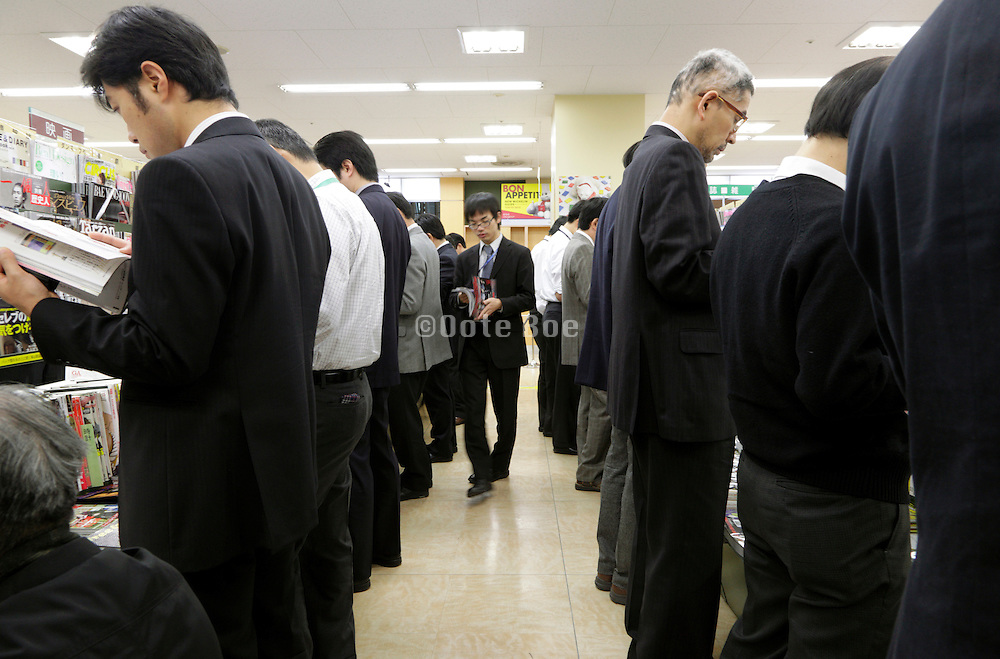 businessmen browsing at a magazine stand Tokyo Japan