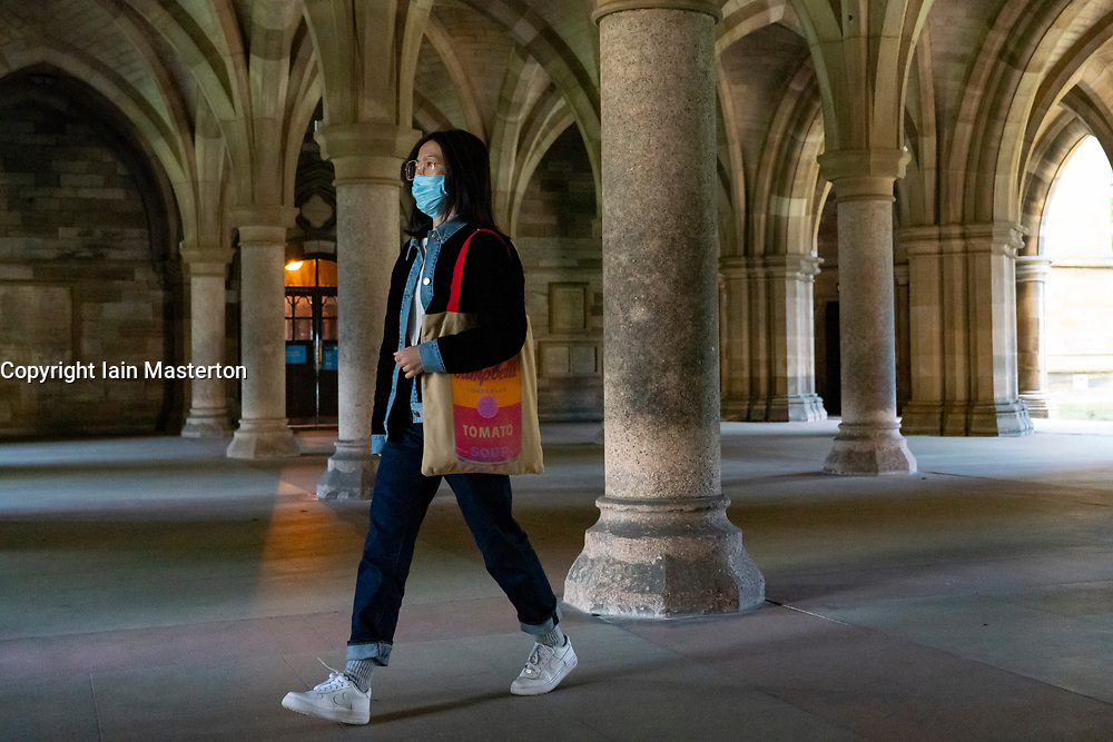 Glasgow, Scotland, UK. 25 September, 2020. Many students at Glasgow University have tested positive for the Covid-19 virus. The Scottish Government has controversially ordered students in several halls of residence where positive cases have spiked, to self-isolate indefinitely. Pictured; Chinese student walking in university cloisters.  Iain Masterton/Alamy Live News