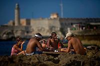 Cuban friends enjoying the sun, playing games on Havana coast.