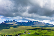 Grey dark cloud formation over the Cuillin mountain range and croft cottages near Coillure on Isle of Skye in the Highlands and Islands of Scotland