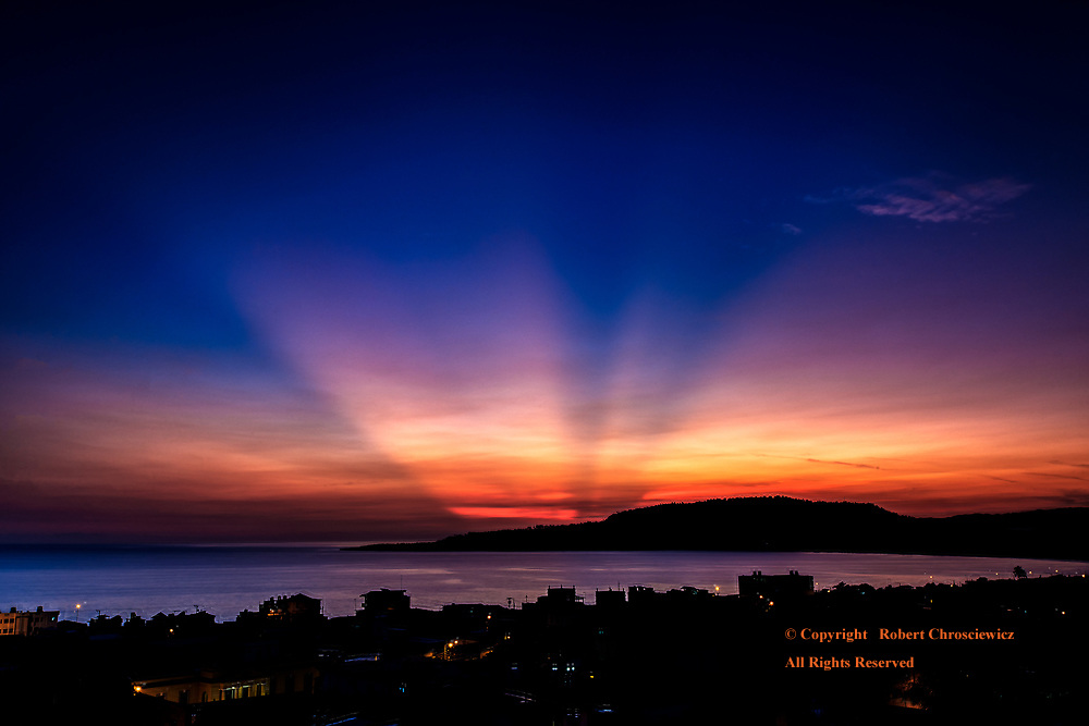 Sunbeams Over Baracoa: Dawn and sunbeams precede the sun in this long exposure photo that overlooks the sleeping city caught in silhouette, Baracoa Cuba.