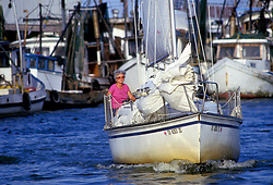 Stock photo of an older woman taking a sail boat out for an enjoyable day on the water.