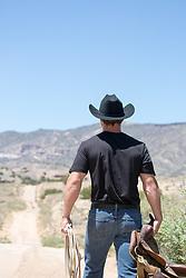 cowboy walking down a dirt road