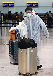 """© Licensed to London News Pictures. 17/03/2020. London, UK. A passenger wears a face mask and protective clothing as he checks in at Heathrow Airport's Terminal Four. The government have advised the public that they should avoid """"non-essential"""" travel and contact with others to curb the spread of the coronavirus. Photo credit: Peter Macdiarmid/LNP"""