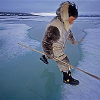 Inuit hunter Jayko Apak jumps open water on Canada's frozen Baffin Bay in search of seal's breathing hole.