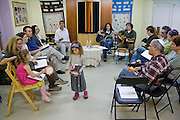Ofer Sabath Beit-Halachmi, a Reform rabbi (center, in white shirt) leads a Shabbat service in a small portable building that is kindergarten by day and synagogue at night near his home in Tzur Hadassah, Israel. (Ofer Sabath Beit-Halachmi is featured in the book What I Eat: Around the World in 80 Diets.) The caloric value of his typical day's worth of food in the month of October was 3100 Kcals. He is 43 years of age; 6 feet, 1 inch tall and 165 pounds. Tzur Hadassah, located 15 minutes southwest of Jerusalem is a communal settlement where residents lease land and houses from the state of Israel for a 99-year period.