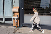 As the second week of the Coronavirus lockdown continues around the capital, and the UK death toll rising by 563 to 2,325, with 800,000 reported cases of Covid-19 worldwide, a young woman walks past a free handwash station fitted for the benefit of the public outside a local business in Clapham High Street, on 1st April 2020, in London, England.