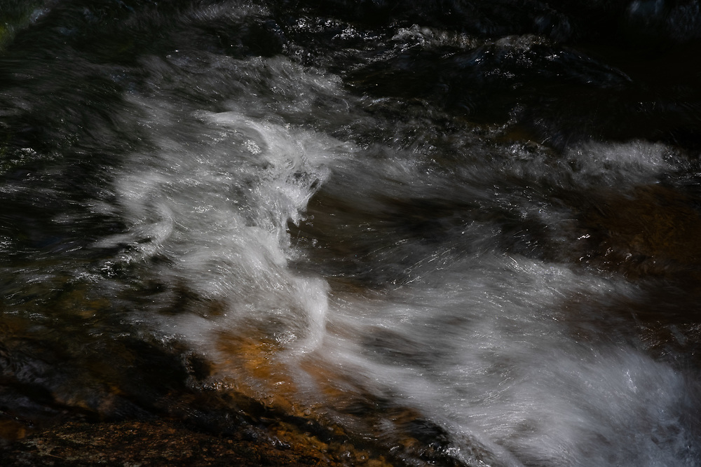 Cold mountain water churning in the woods of New Hampshire's White Mountains.