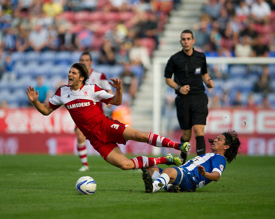 Middlesbrough's George Friend is tackled by Wigan Athletic's Roger Espinoza<br /> <br /> Photo by Stephen White/CameraSport<br /> <br /> Football - The Football League Sky Bet Championship - Wigan Athletic v Middlesbrough - Sunday 25th August 2013 - DW Stadium - Wigan<br /> <br /> © CameraSport - 43 Linden Ave. Countesthorpe. Leicester. England. LE8 5PG - Tel: +44 (0) 116 277 4147 - admin@camerasport.com - www.camerasport.com
