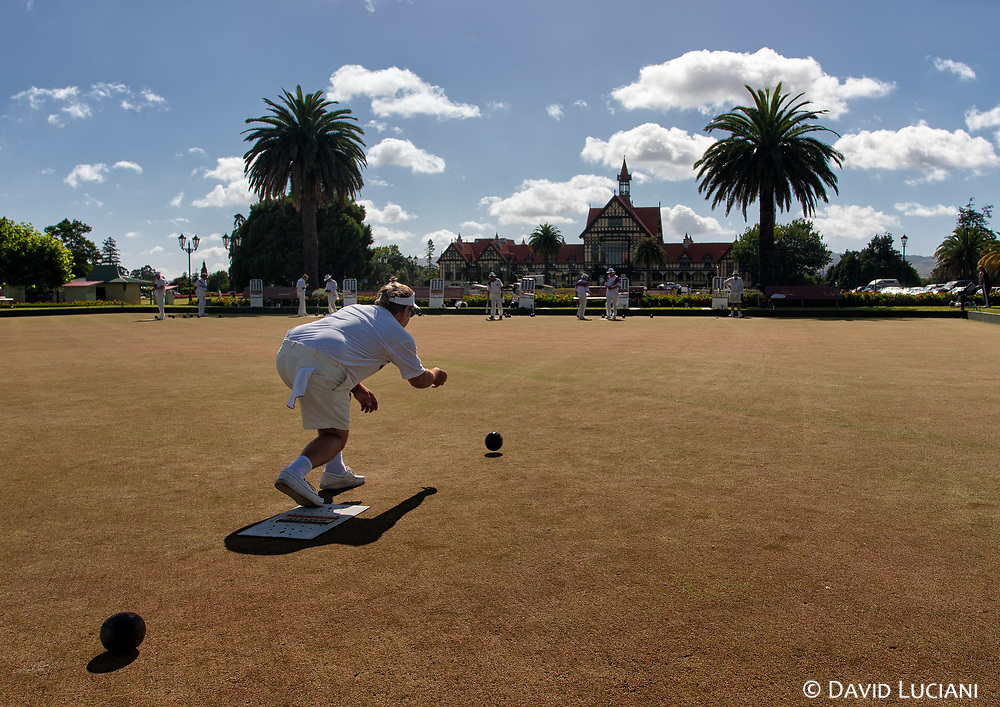 A man playing outdoor lawn bowling in Rotorua's colonial Government Gardens, set near the bathhouse building.