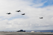 A formation of four F/A-18 E/F Super Hornets pass over the deck of the USS Abhram Lincoln.