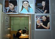 "Radio producer Shanshan makes a phone call while recording the program ""Kejia Xiangqing"" in Kejia, or Hakka language in Beijing November 19. . Photo by Natalie Behring"