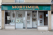 "Mortimer vacated shop window ""Market Gardeners since 1897"" displaying paintings by a pet portrait artist, Dursley.Recession 2010: Parsonage Street, Dursley, Gloucestershire shops closed due to economic downturn."