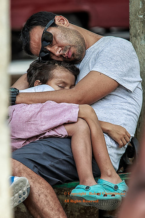 Asleep Together: A young father and daughter sleep in each other's arms, while sitting on a park bench in the busiest part of Havana Cuba