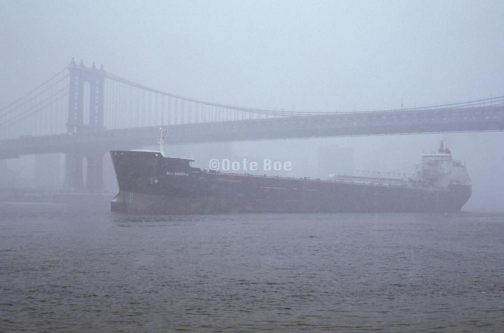 large cargo ship under Manhattan Bridge