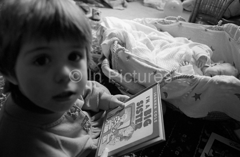 A 2 year-old girl reads a book about being a big sister, coming to terms with role-play, the idea of having a newborn baby brother in his basket at home in south London. The siblings are in their south London home, the girl sitting up on the carpet and her brother - only a few weeks old - is starting to wake from a mid-morning sleep. The book being read is 'I'm a big sister' by writer Joanna Cole, written to help young girl's overcome the shock of suddenly no longer being the most important member of a young family, helping her deal with a new status as the eldest but more mature child.